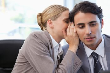 Businesswoman whispering something to her colleague in a meeting room